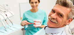 An older man smiling with an implant dentist in St. Peters