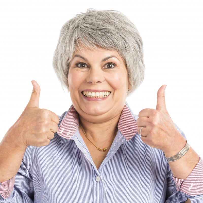 older woman smiling with thumbs up
