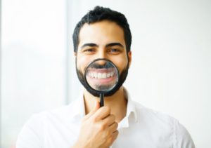 man in white shirt holding magnifying glass to his smile