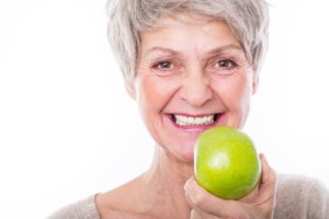 Older woman with dental implants holding an apple.